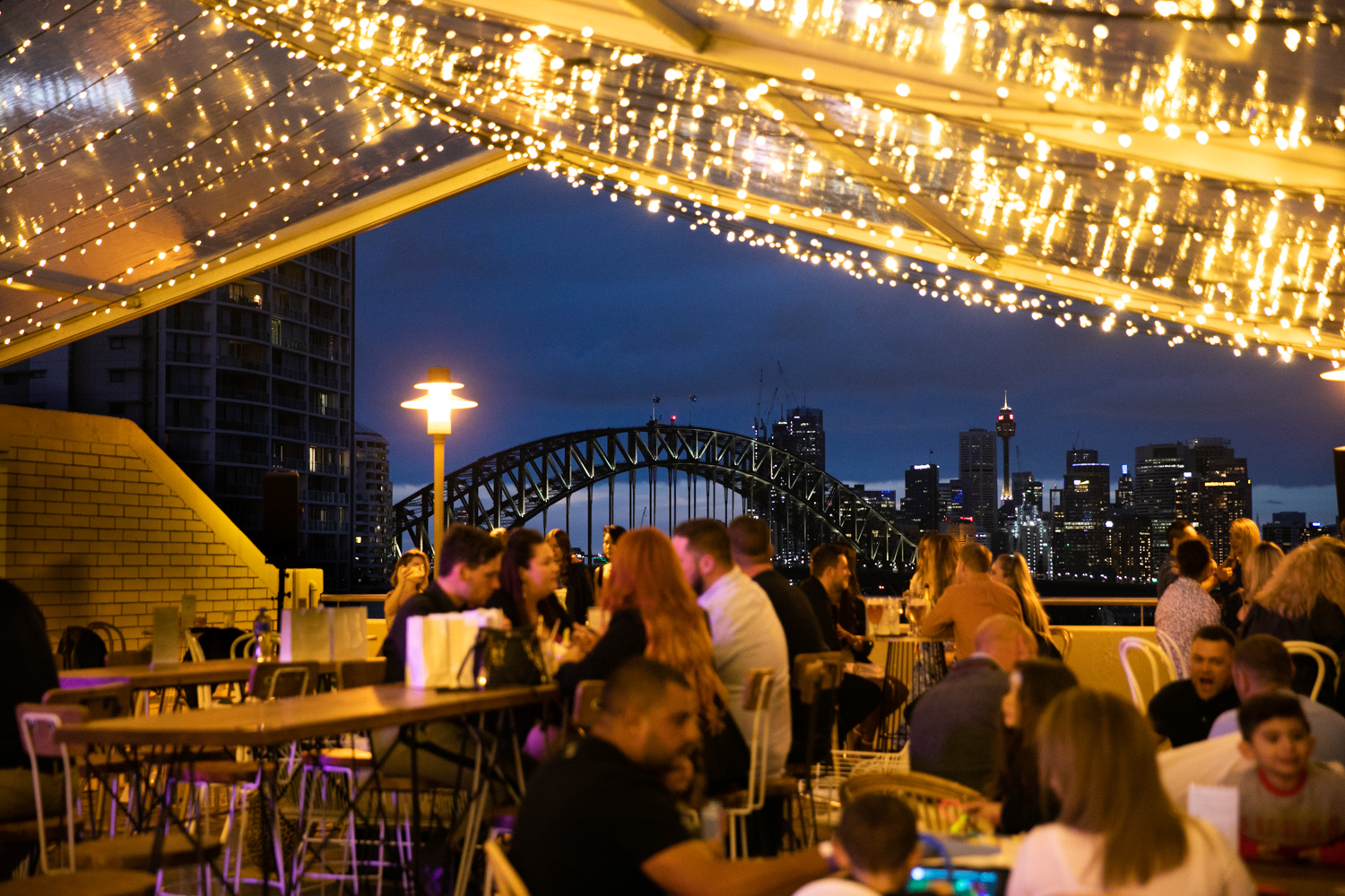 People dining at an outdoor New Year's Eve party with Sydney Harbour Bridge in background